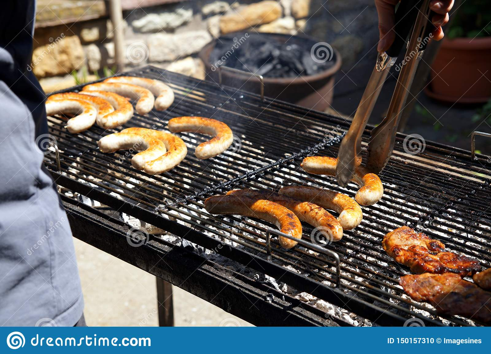 Delicious row of pork bratwurst and grilled meat over the coals on barbecue.lifting a pair of tongs in a view of his hand.