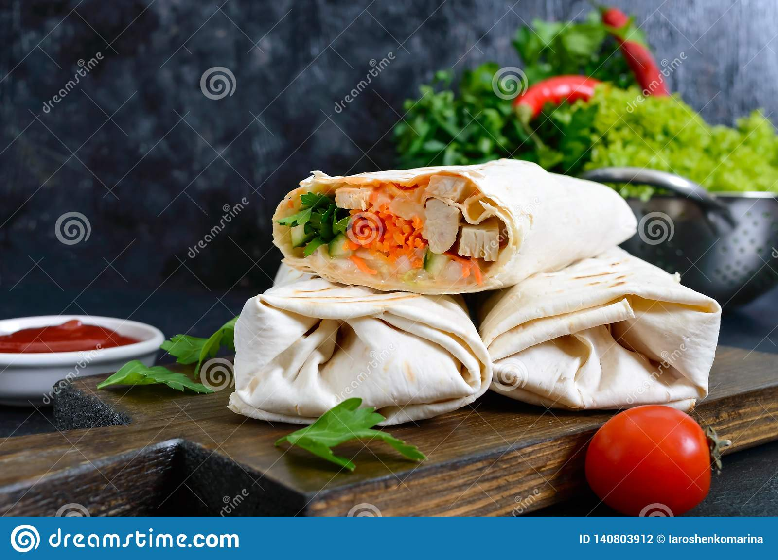 Delicious shawarma sandwich on a black background. Burritos wraps with grilled chicken and vegetables, greens.