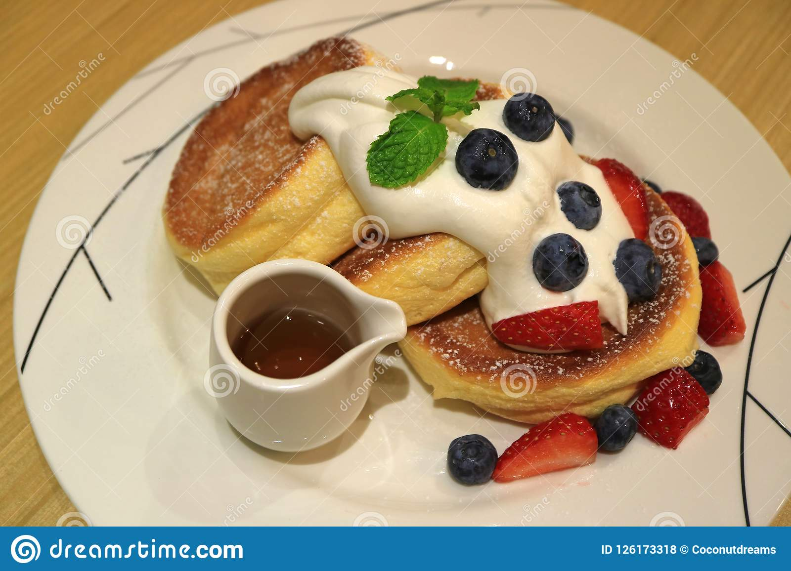 Delicious Souffle Pancake with Maple Syrup, Fresh Whipped Cream and Mix Berries Served on white Plate