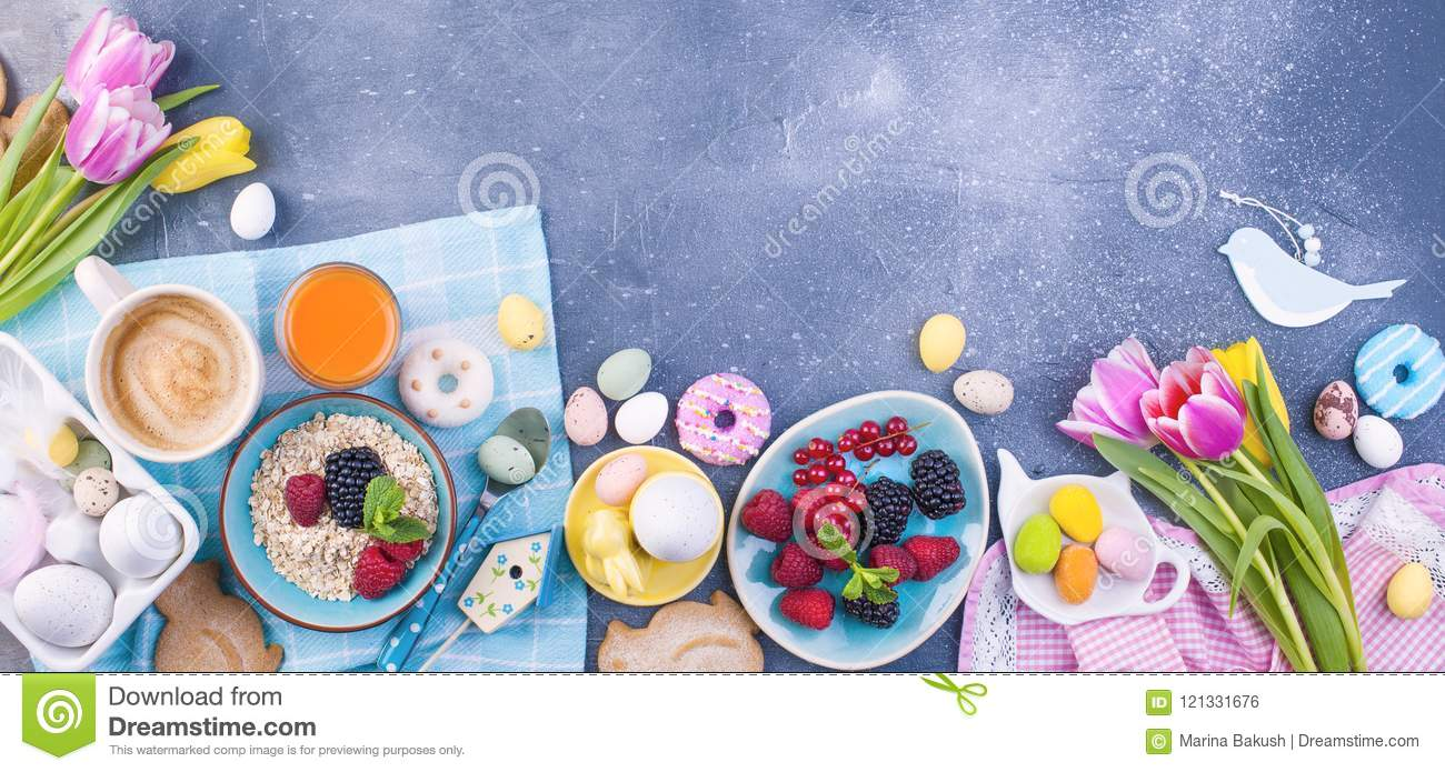 Delicious spring breakfast on a gray stone background. A bouquet of fresh tulips of pink and mint color. Small and large colored