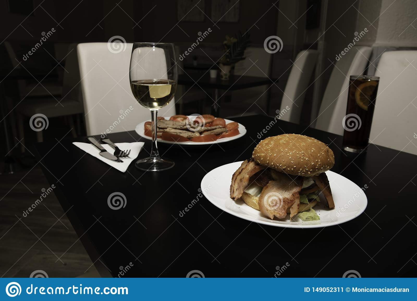 Delicious table set to eat, a delicious burger with a glass of wine and another dish more