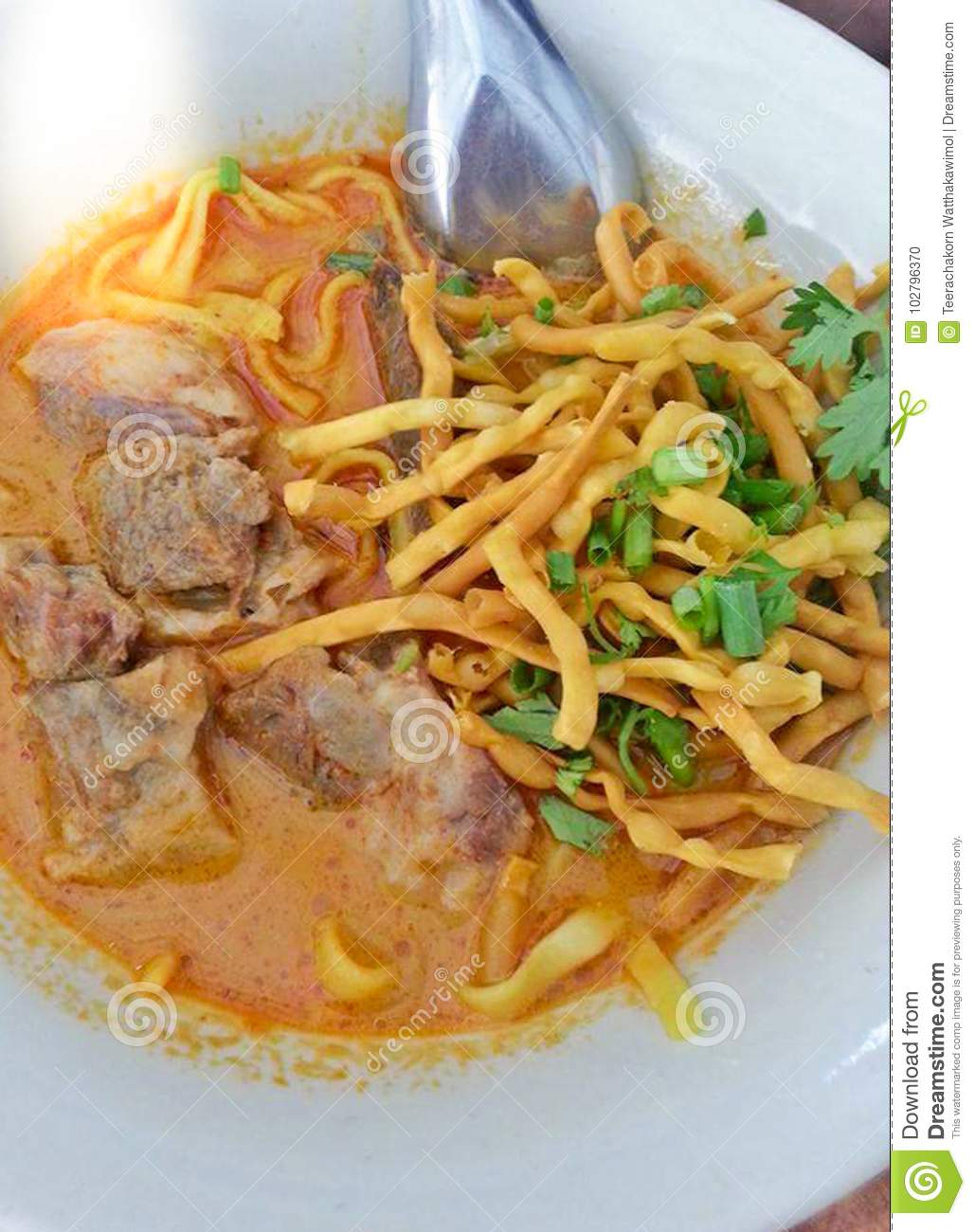 Delicious tasty Thai Northern Style Curried Noodle Soup with Beef in a bowl Khao Soi, Northern Thailand Food background close up