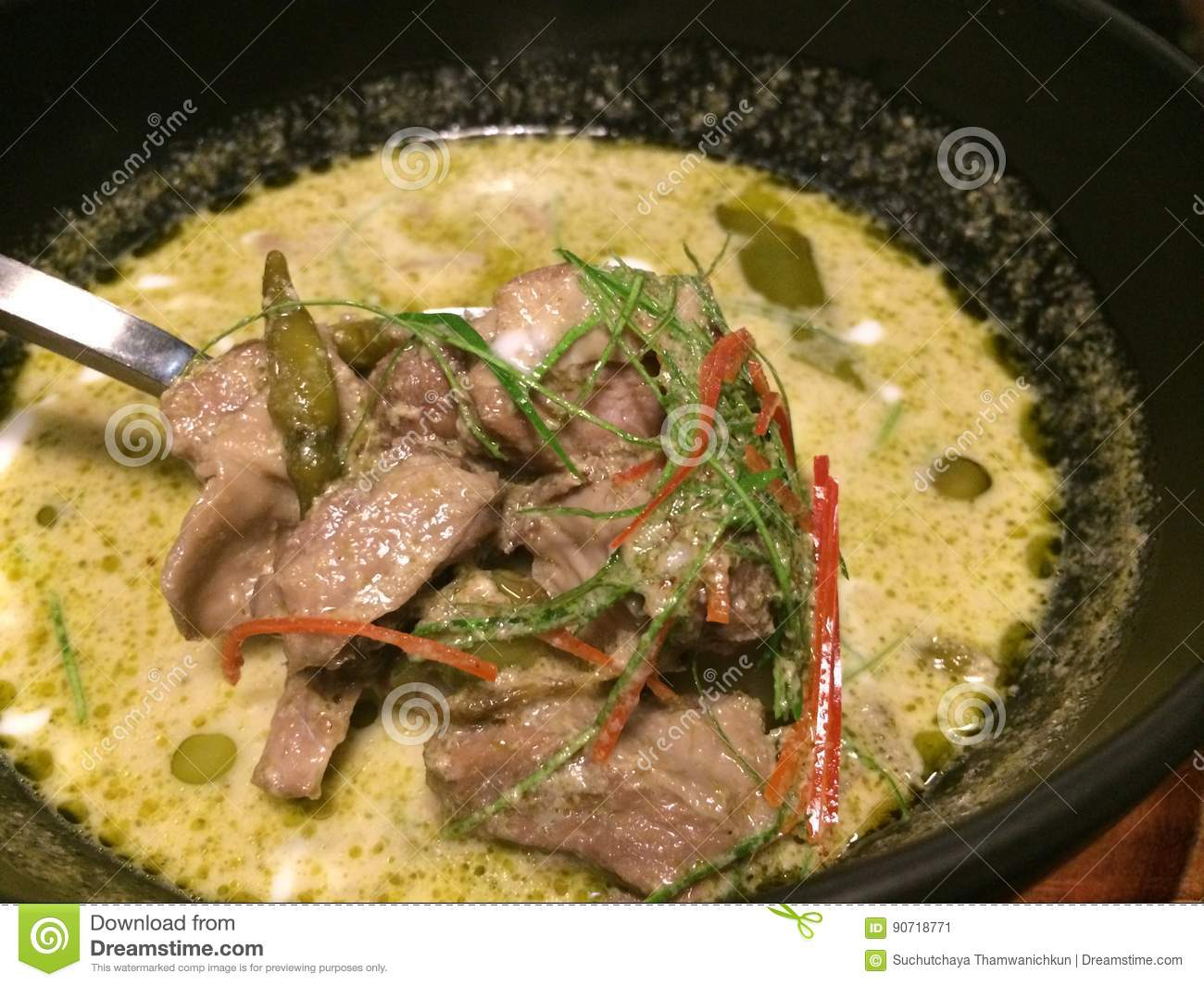 Delicious thai beef green curry in Thai restaurant, lade with spoon to highlight, focus-on-foreground, closed-up shot