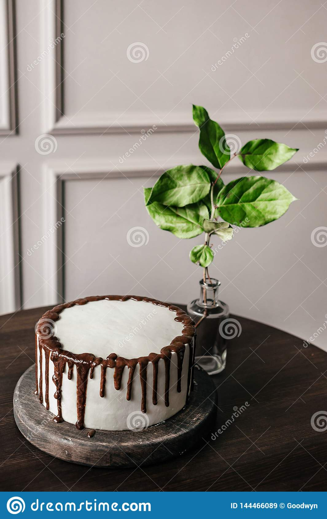 Delicious white cake with chocolate on a wooden stand. Next is a vase with a leaf.
