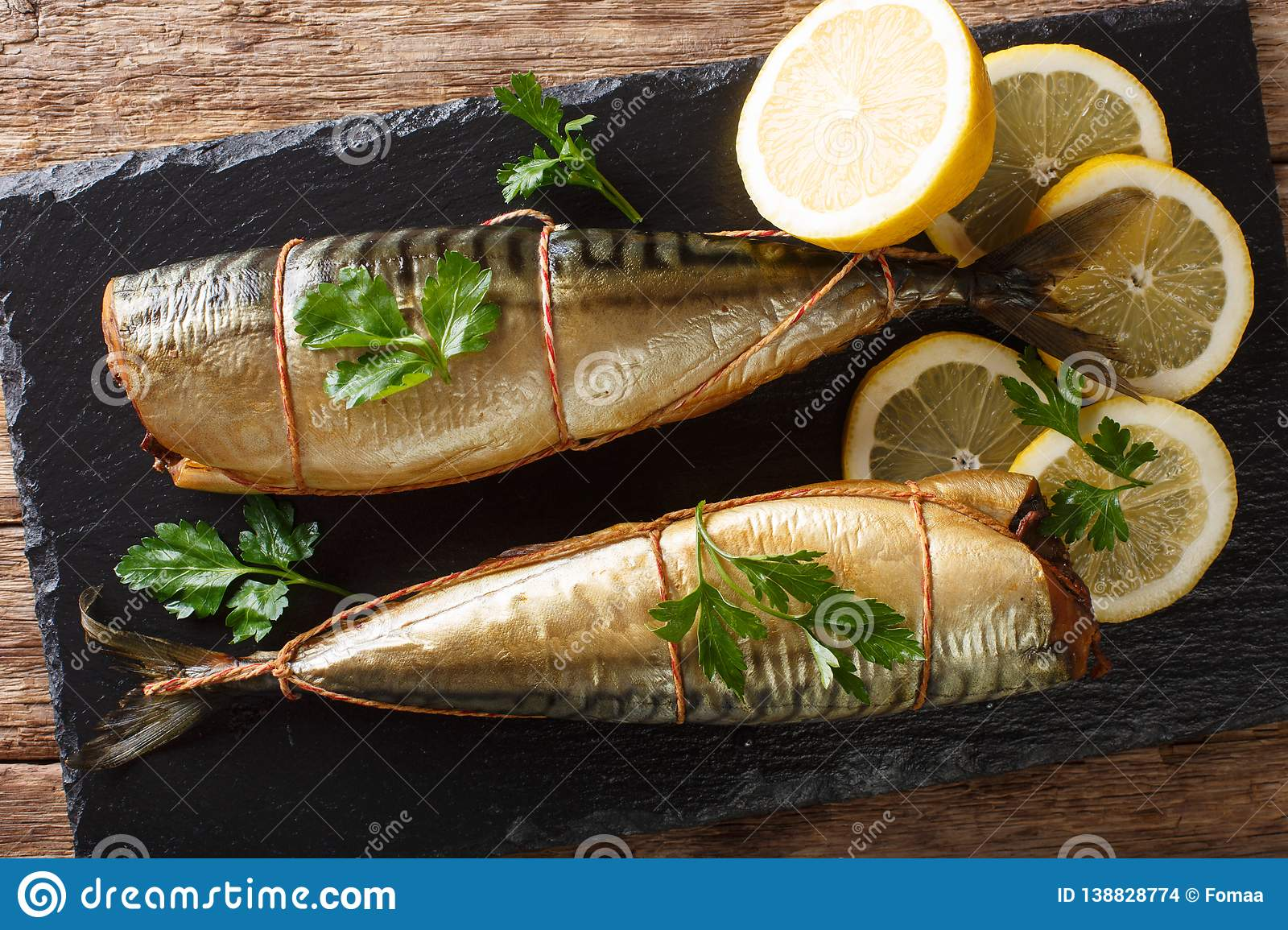 Delicious whole smoked mackerel with lemons and parsley closeup on a black slate board. Horizontal top view