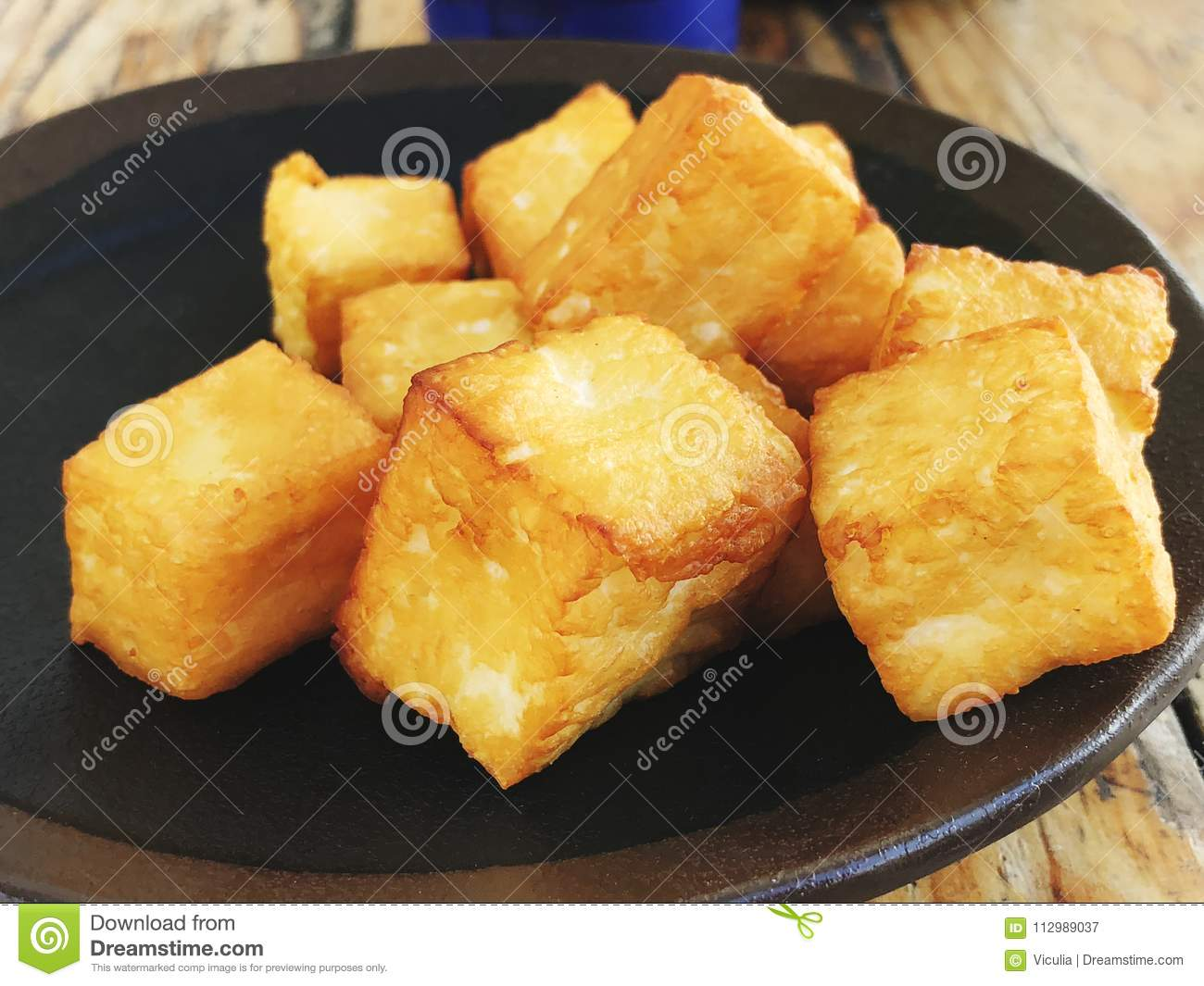 Deliciously fried cheese cubes on a dark plate.