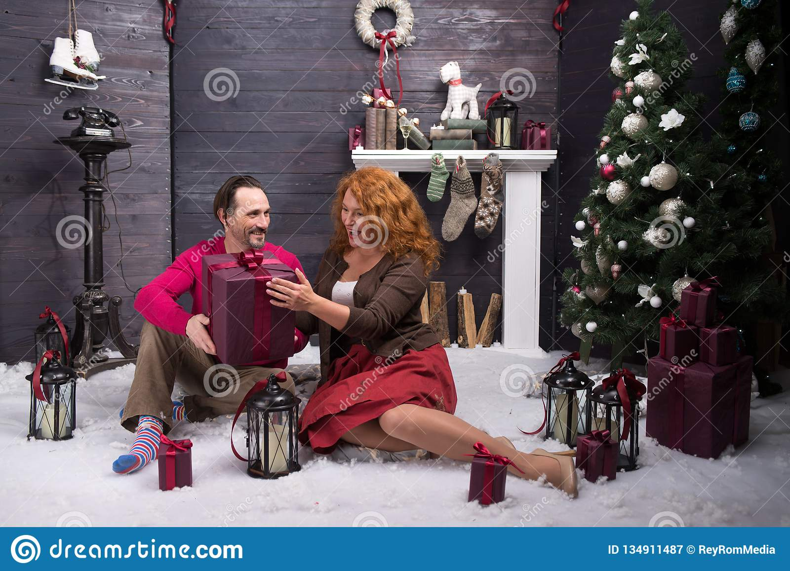 Excited mature woman being pleased with Christmas present from her husband