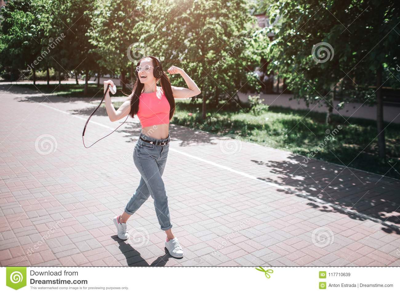 Delightful and happy person is dancing on street. She is listening to music through headphones and using player for that