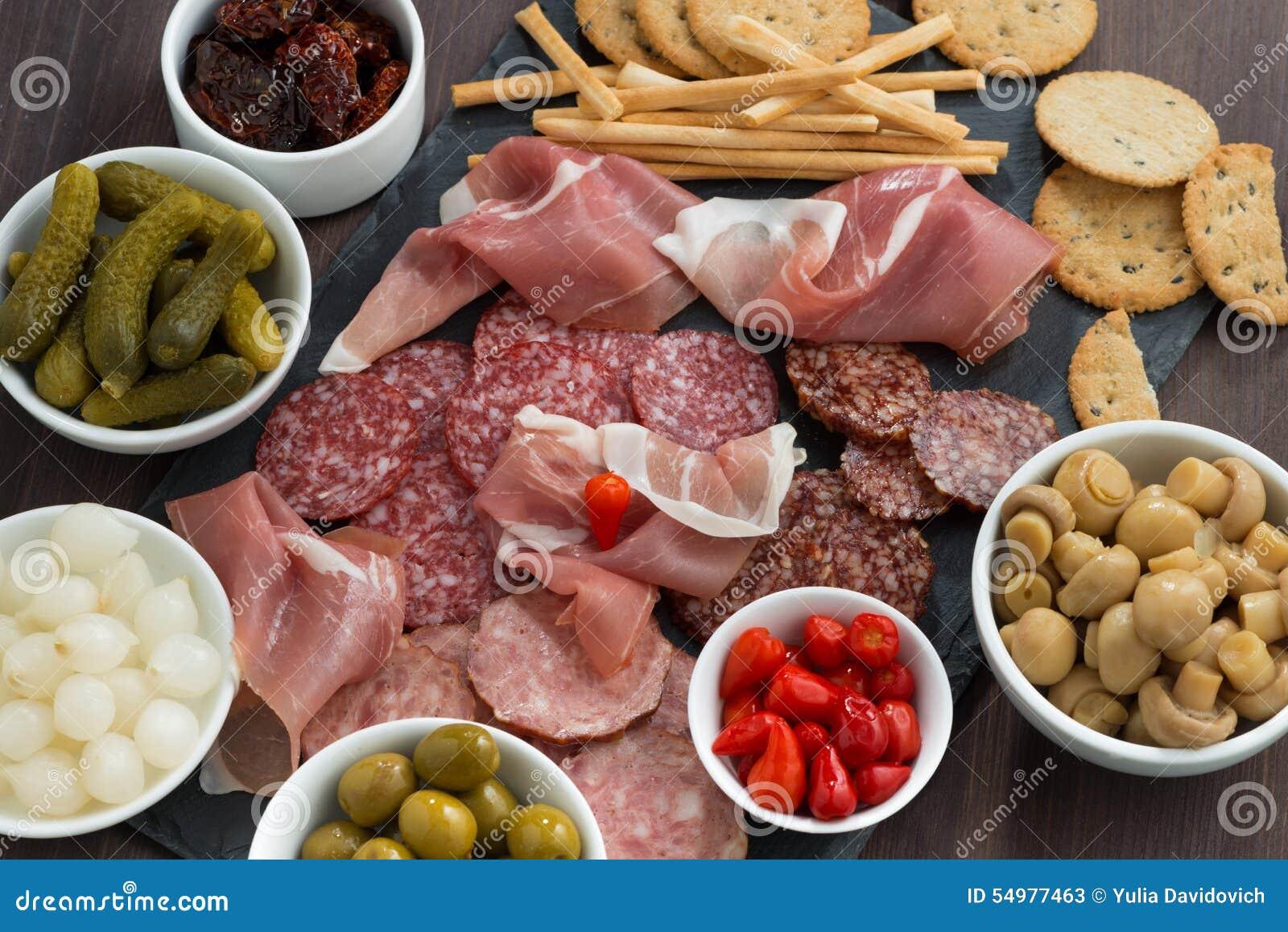Delikatessaffärköttmellanmål, korvar och knipor på en svart tavla, närbild