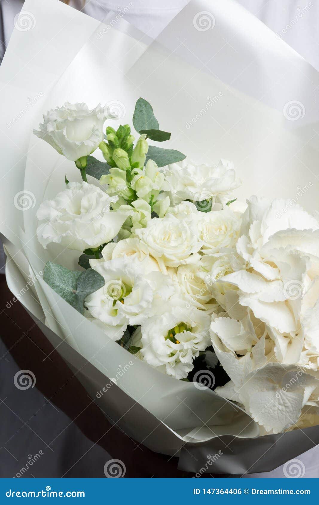 Delikatny bukiet zieleni i biali kwiaty, poślubia bridal bukiet na szarości ścianie
