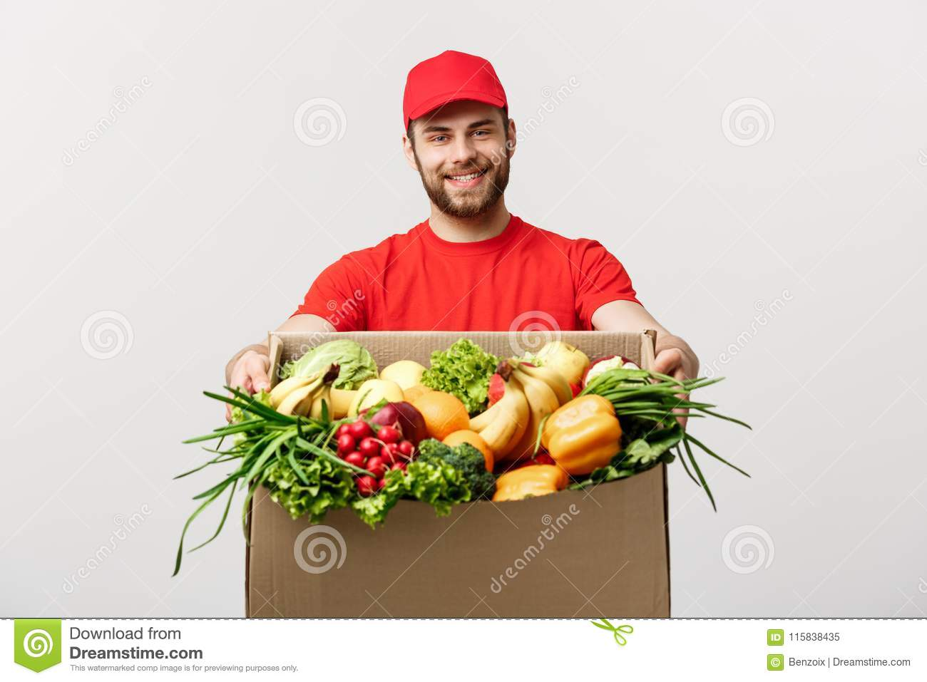 Delivery Concept - Handsome Cacasian delivery man carrying package box of grocery food and drink from store. Isolated on