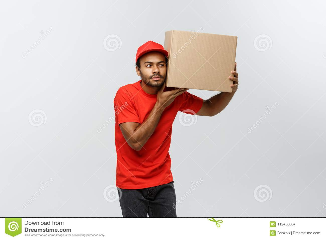 Delivery Concept - Portrait of Curious African American delivery man listen inside a box package. Isolated on Grey