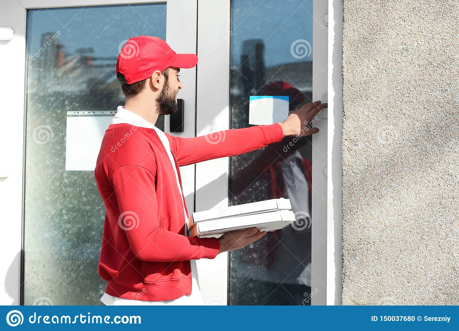 Delivery man with cardboard pizza boxes near house of customer outdoors