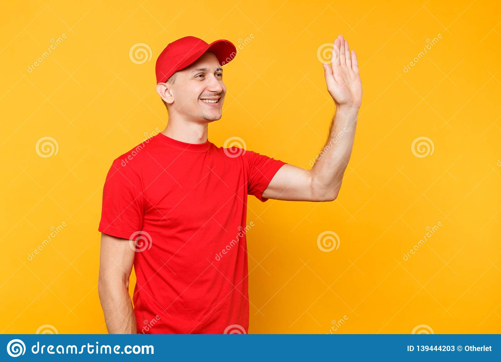 Delivery man in red uniform isolated on yellow background. Smiling male employee in cap, t-shirt courier dealer waving