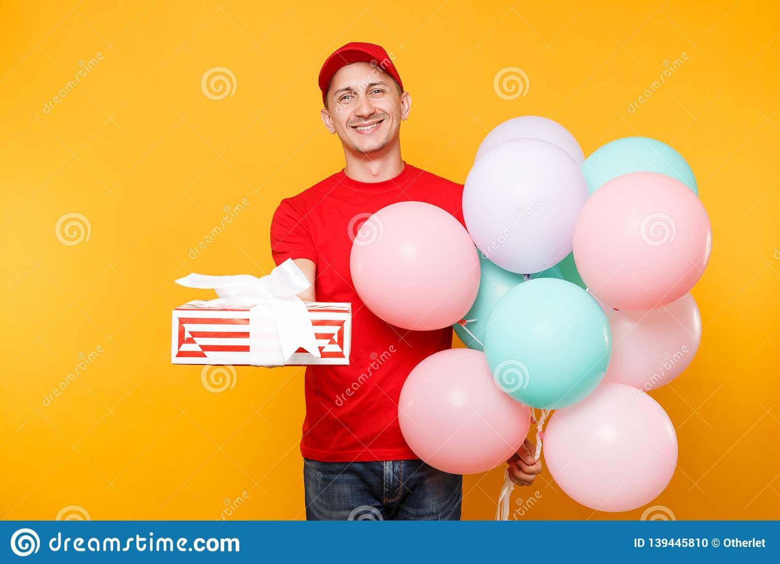 Delivery man in red uniform isolated on yellow orange background. Male employee in cap, t-shirt courier dealer holding