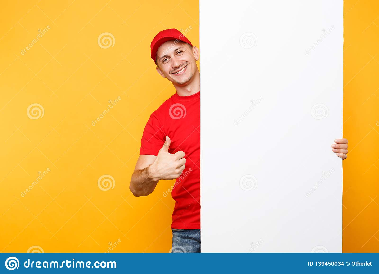 Delivery man in red uniform isolated on yellow orange background. Male employee courier in cap, t-shirt holding big