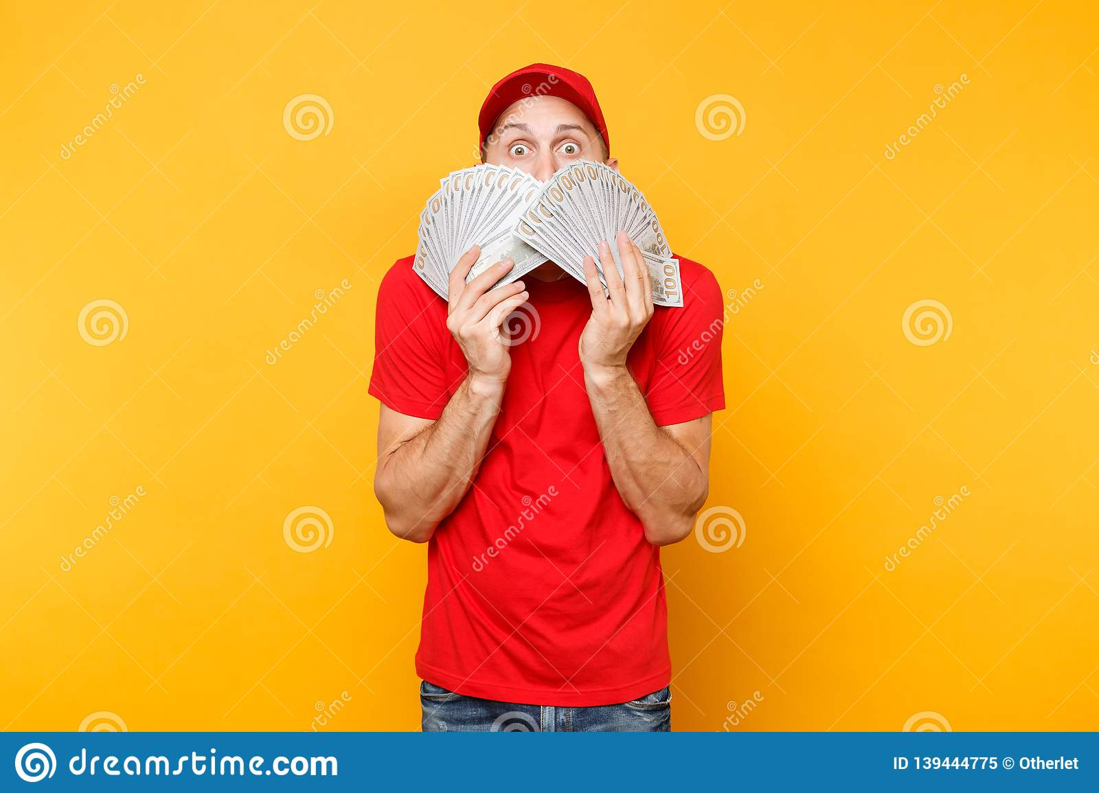 Delivery man in red uniform isolated on yellow orange background. Professional male employee in cap, t-shirt courier or