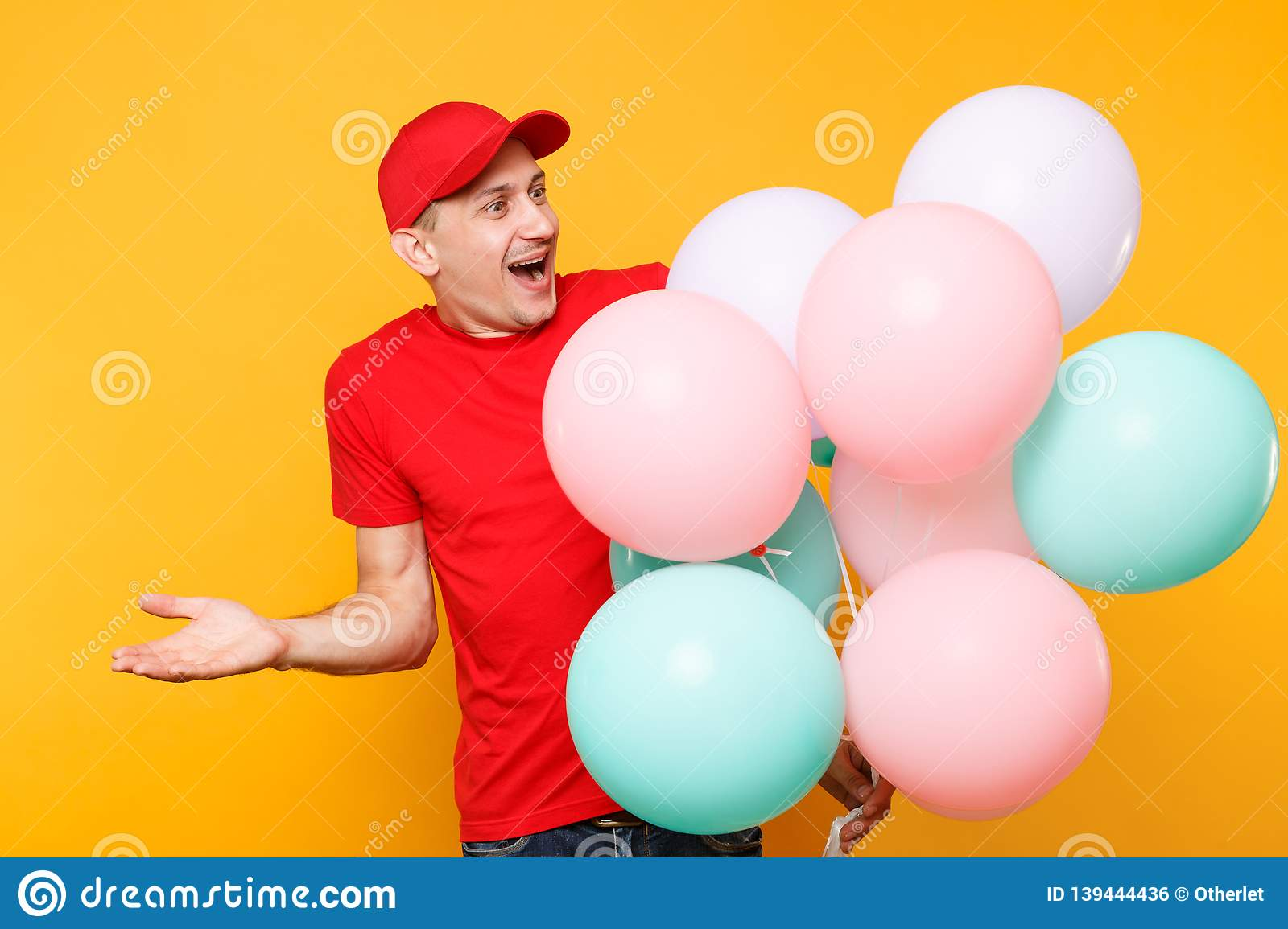 Delivery man in red uniform isolated on yellow orange background. Professional male employee in cap, t-shirt courier