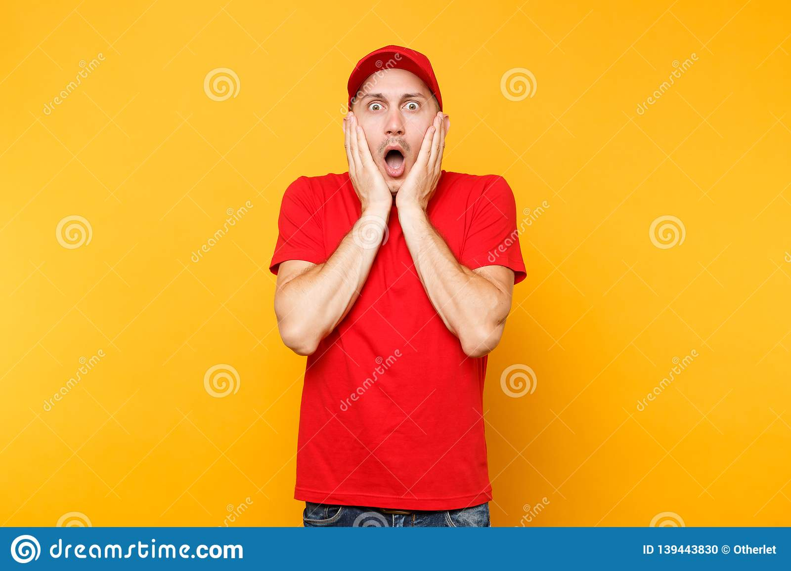 Delivery man in red uniform isolated on yellow orange background. Professional scared shocked male employee in cap, t