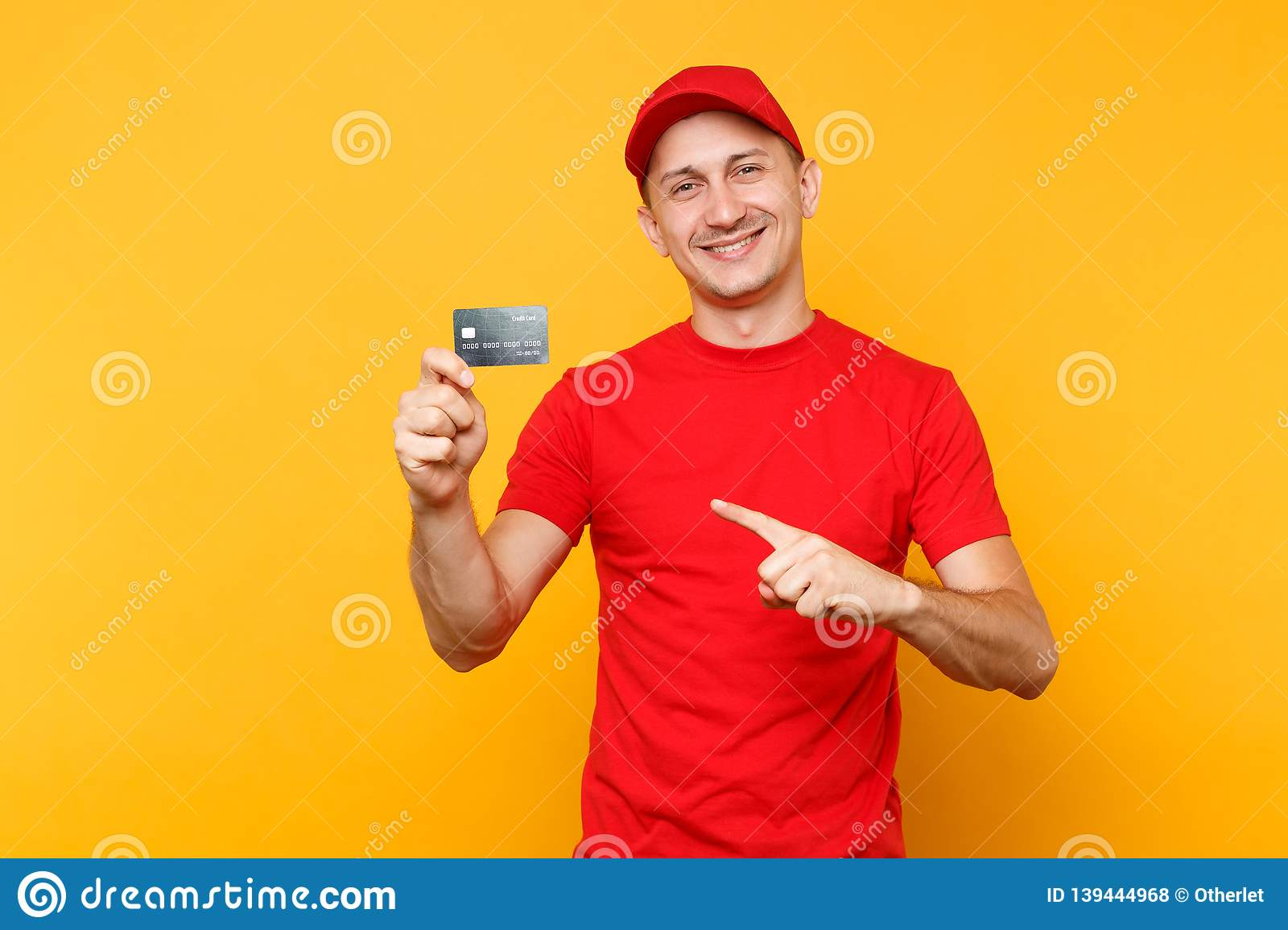 Delivery man in red uniform isolated on yellow orange background. Professional smiling male employee in cap, empty t