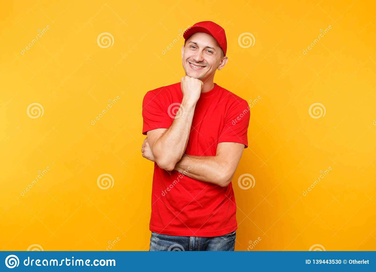 Delivery man in red uniform isolated on yellow orange background. Professional smiling male employee in cap, t-shirt