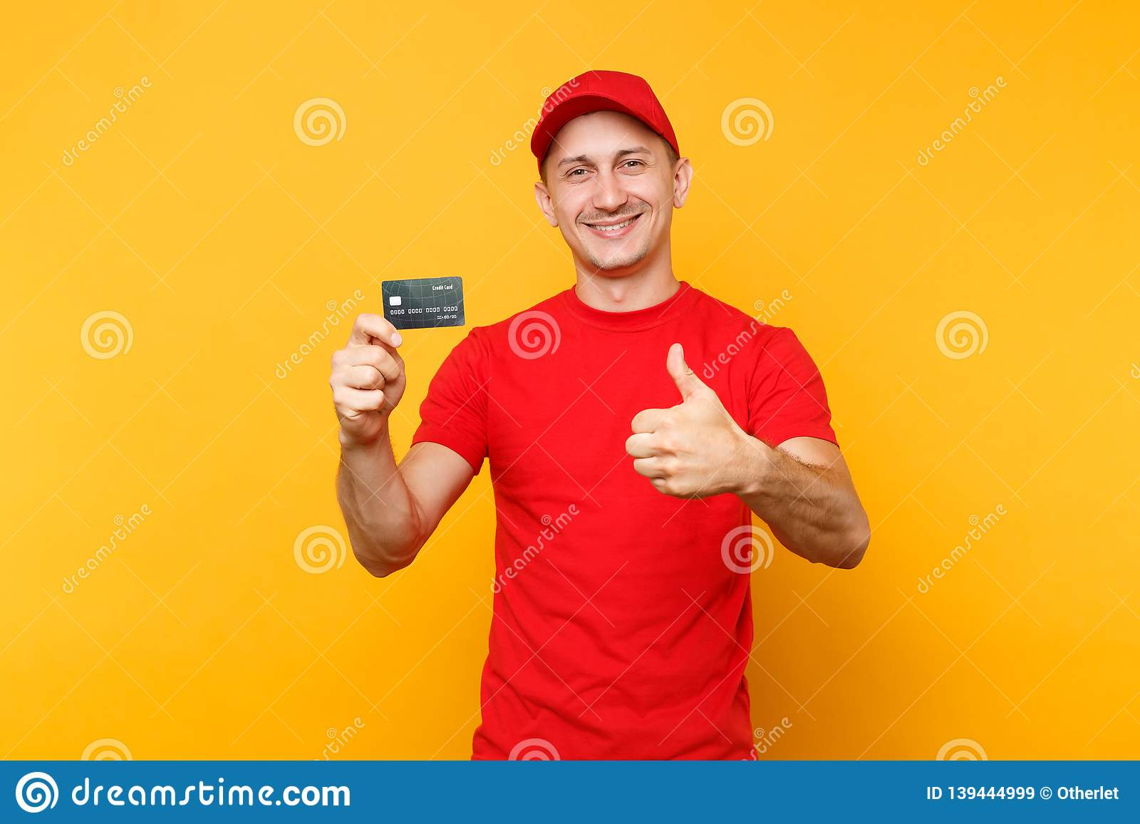 Delivery man in red uniform isolated on yellow orange background. Smiling male employee in cap, empty t-shirt courier