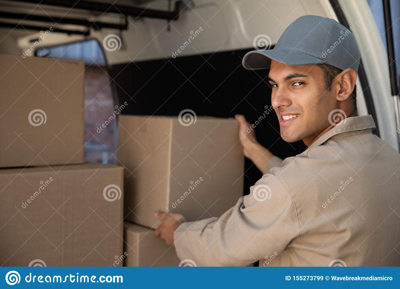 Delivery man unloading cardboard boxes from a van outside the warehouse