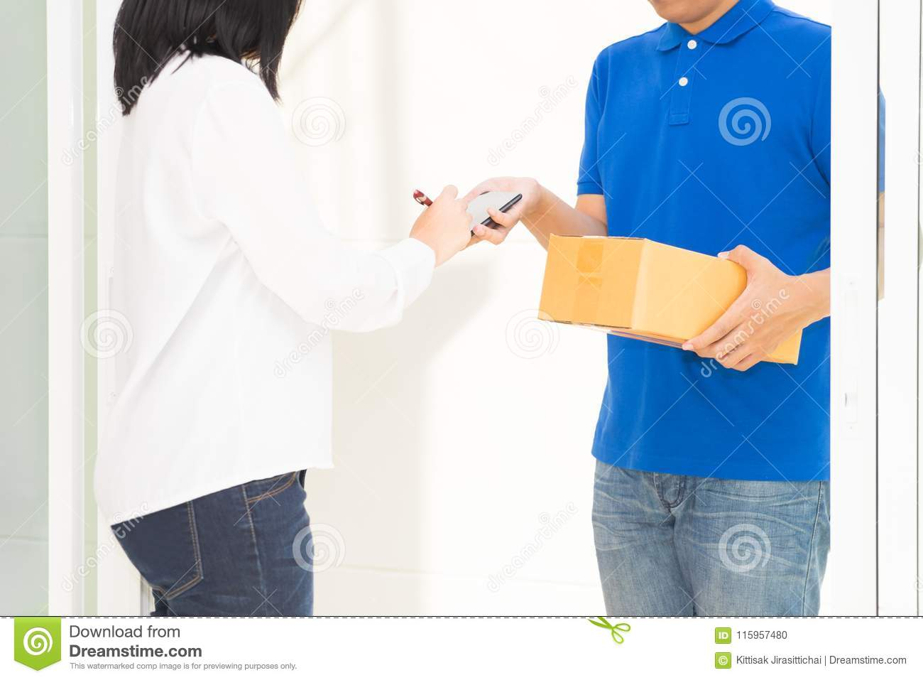 Delivery man pointing on smartphone and woman receiving package