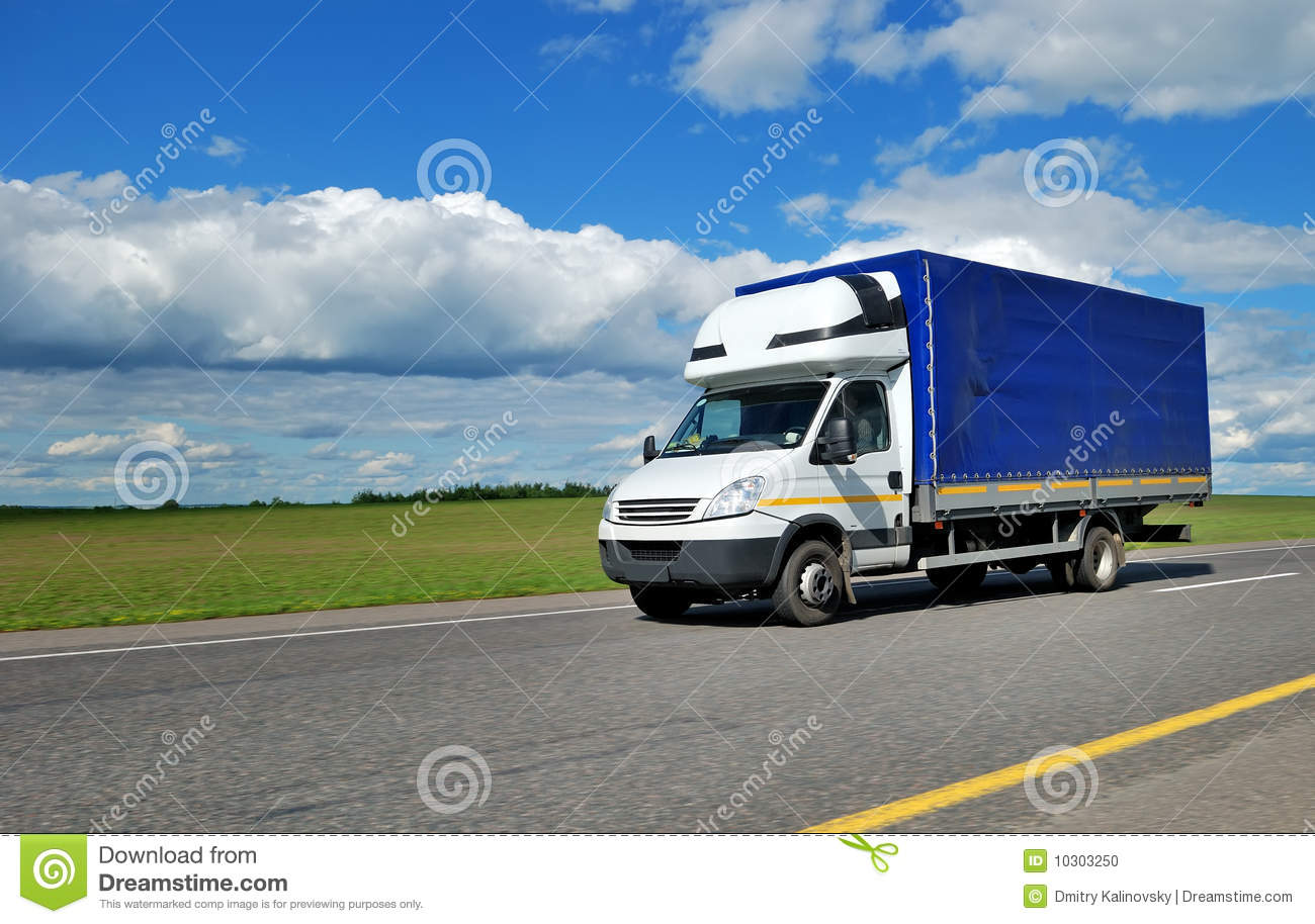 Yellow delivery truck outdoor on the highway over blue cloudy sky. See ...