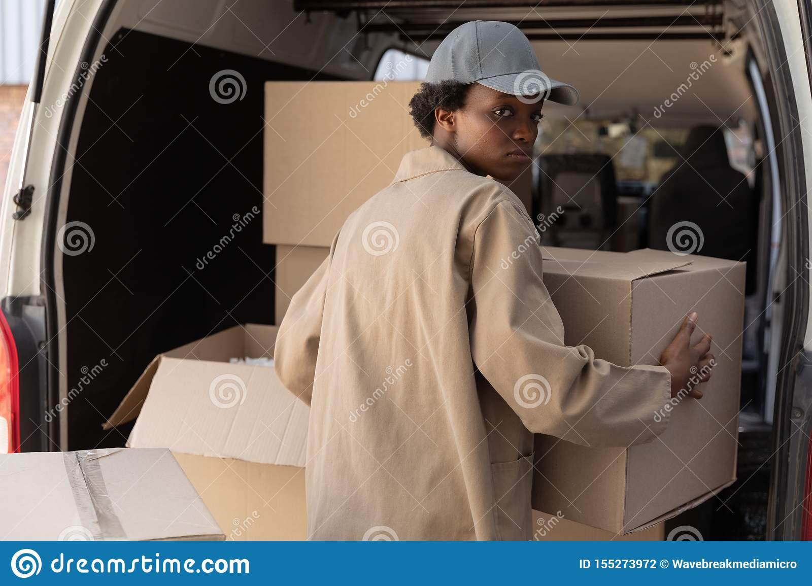 Delivery woman unloading cardboard boxes from a van outside the warehouse