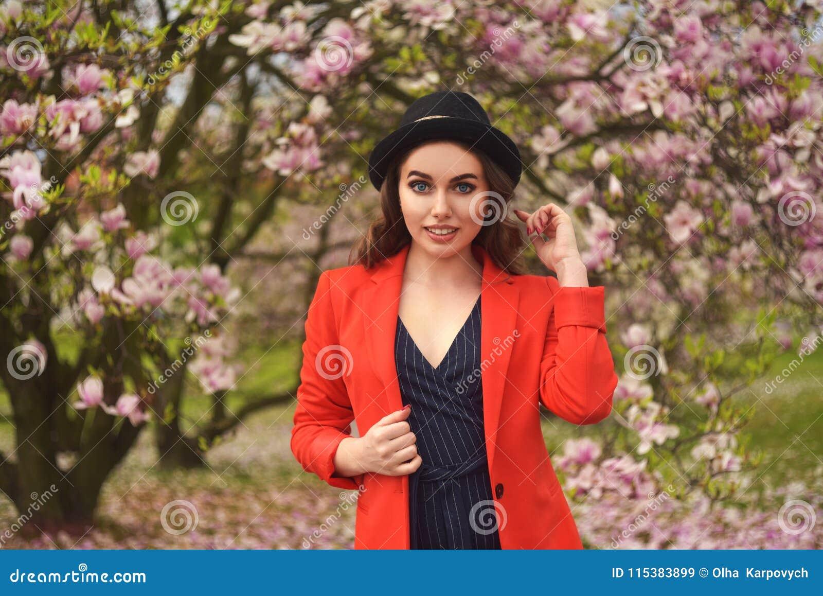 Della primavera di modo della ragazza ritratto all aperto in alberi di fioritura Donna romantica di bellezza in fiori Signora sen