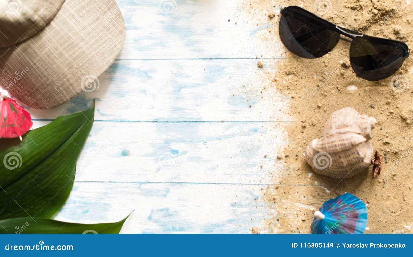 Della spiaggia vita ancora Vetri neri con gli ombrelli del cocktail, conchiglia sulla sabbia su un fondo di legno