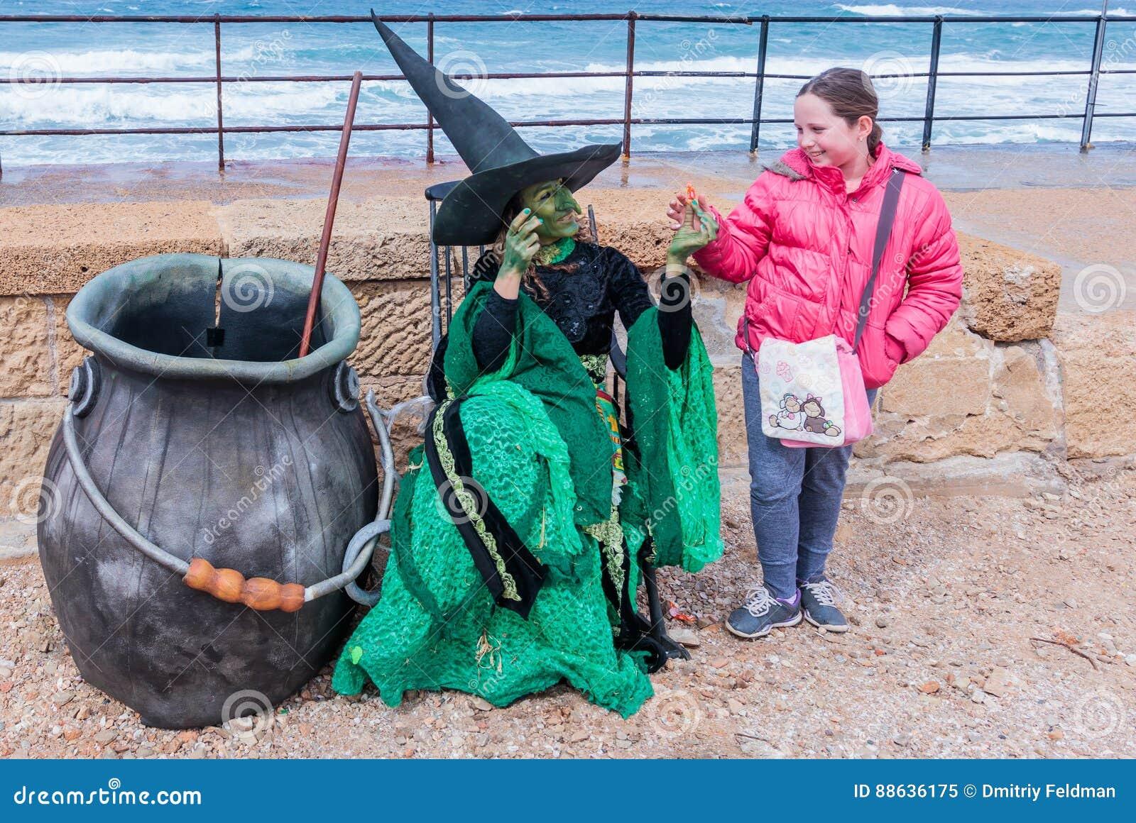 Deltagaren av festivalen som kläs som häxa, ger flickagodisen