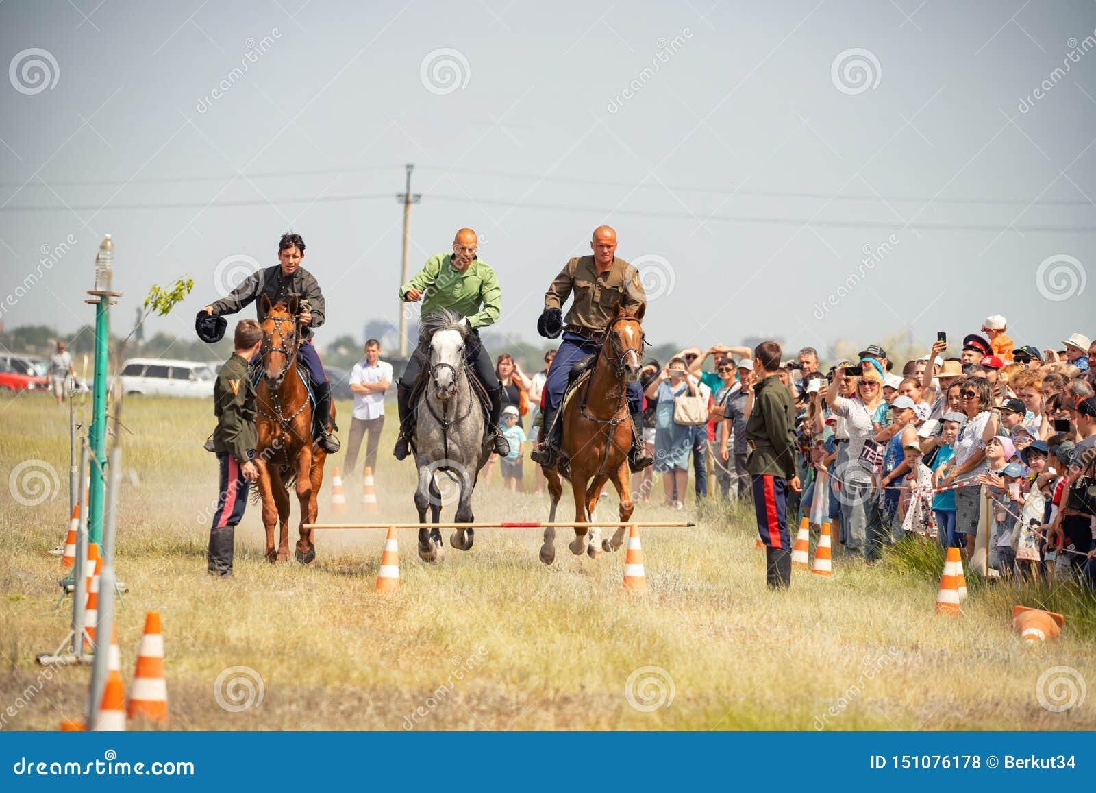 Demonstração da capacidade dos cossacos dos representantes para ficar na sela e para executar a cavalo truques