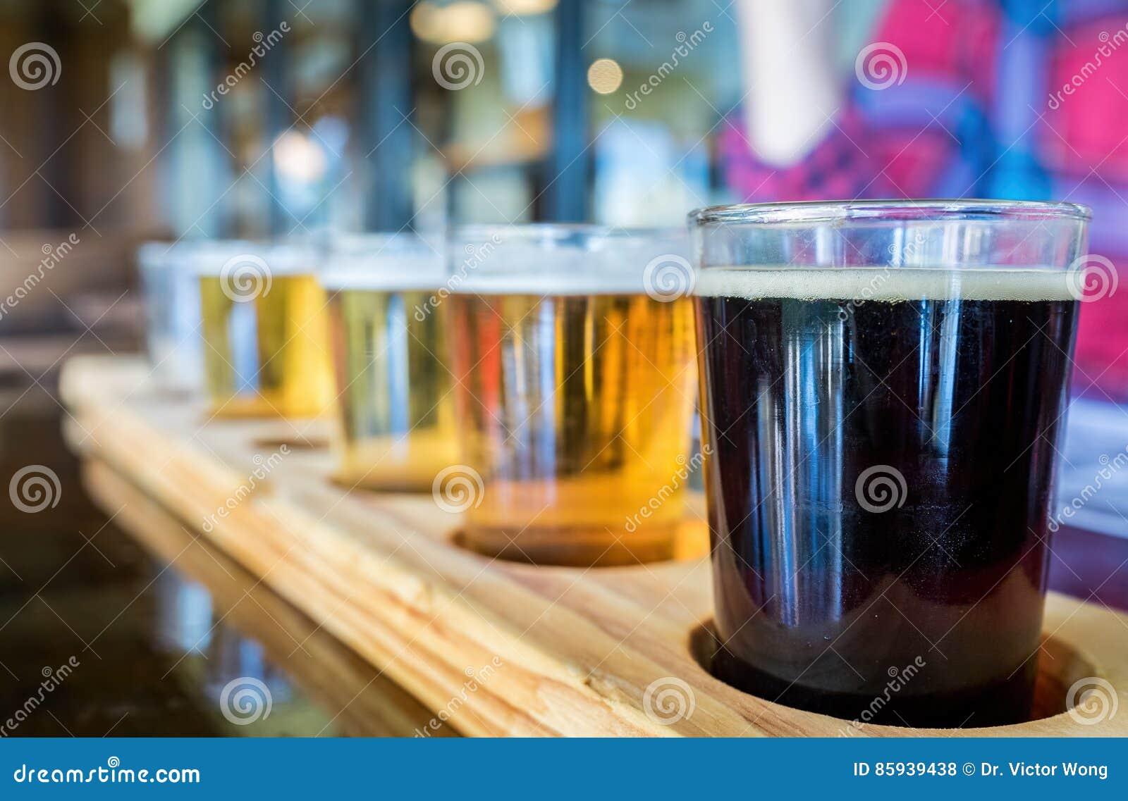 Demonstradores da cerveja na bandeja de madeira original