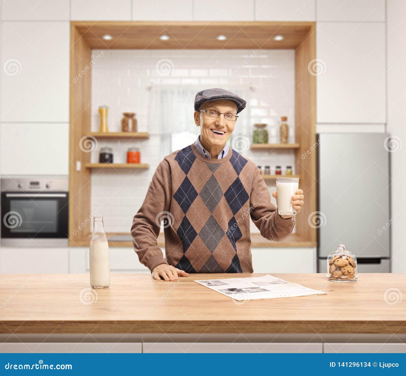 Den äldre mannen som rymmer ett exponeringsglas av, mjölkar och anseendet bak en träräknare i ett kök