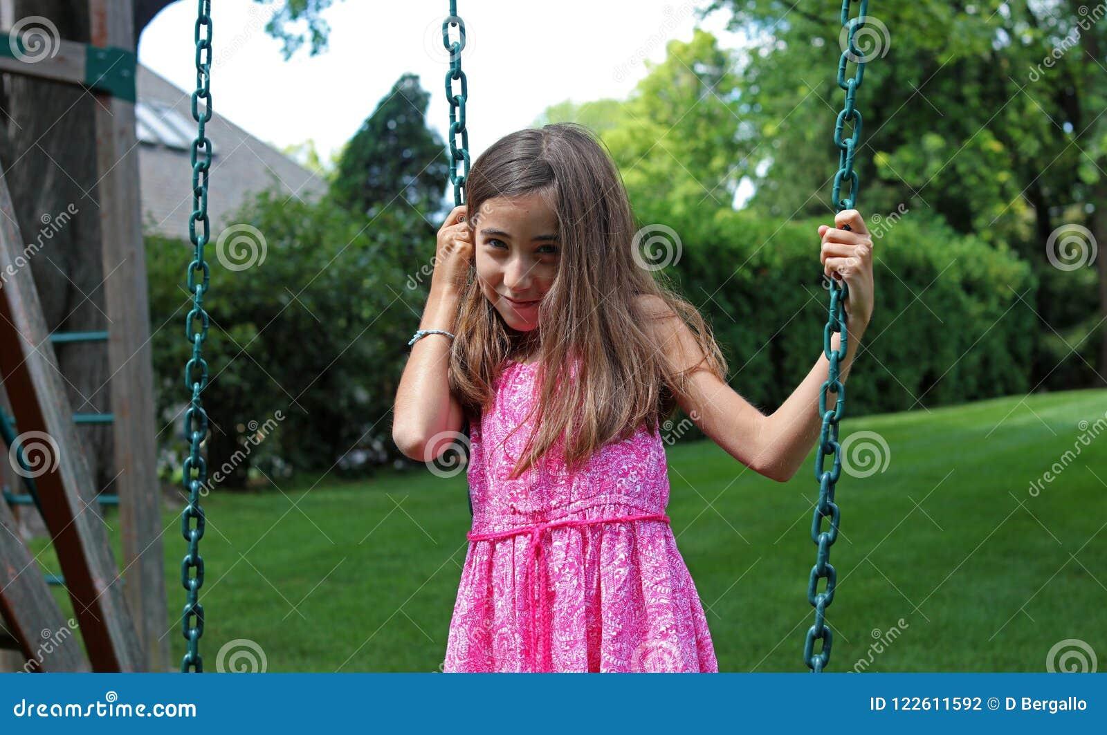 Den älskvärda lilla flickan på gungor i parkera med rosa färger klär under sommar i Michigan