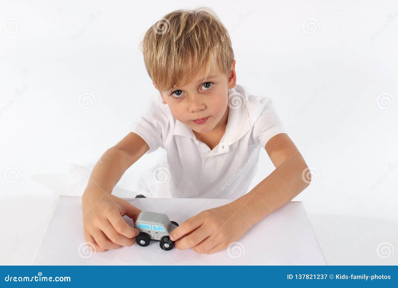Den änglalika seende pojken visar hans favorit- träbilleksak och önskar att spela