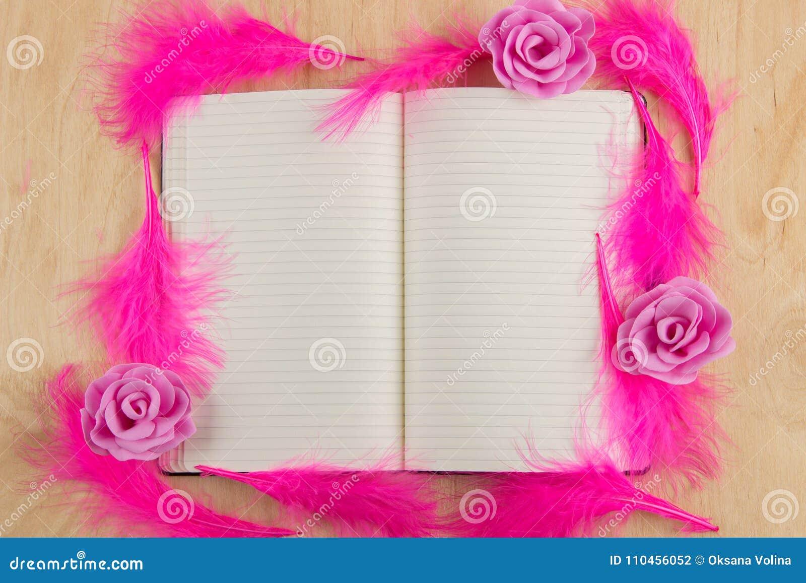 Den öppna anteckningsboken med vita sidor och rosa färger befjädrar på en träflik