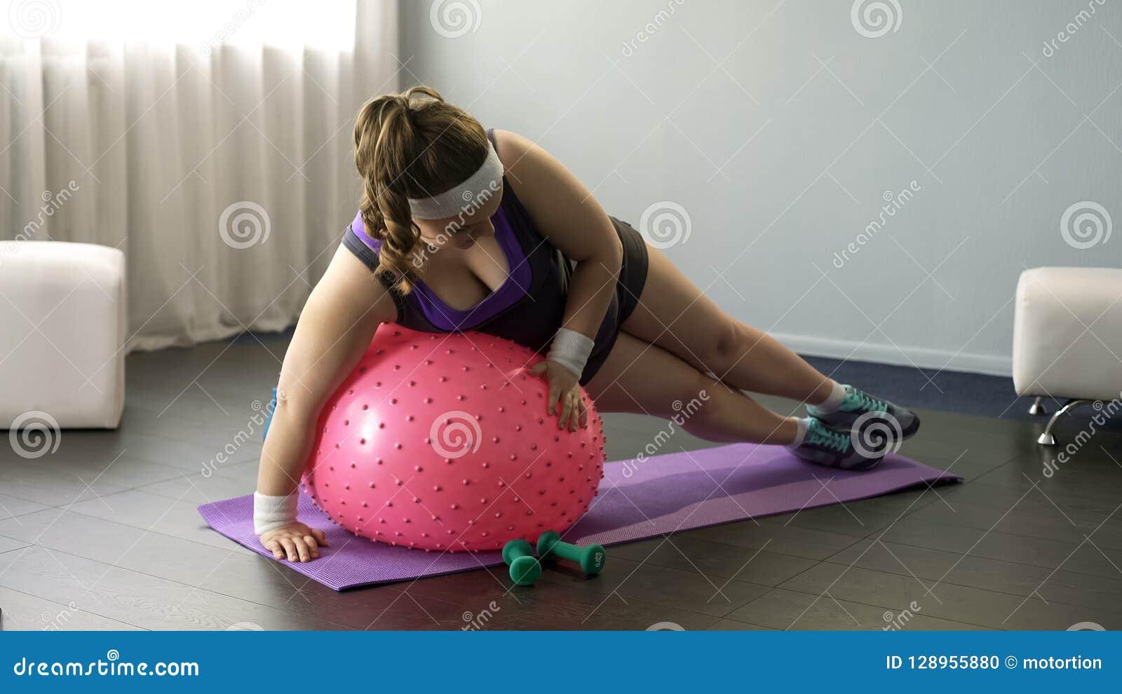 Den överviktiga damen som försöker att göra övningar på kondition, klumpa ihop sig och att göra roliga försök