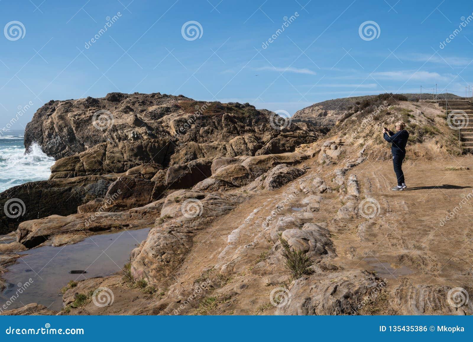 Den aktiva höga kvinnan står på det halt vaggar av punktLobos den statliga reserven i Kalifornien och att beundra landskapet och