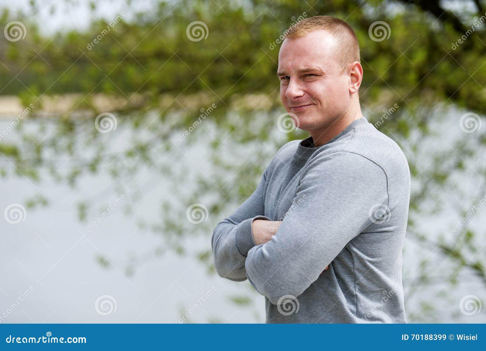 Den aktiva mannen med den idrotts- kroppen och korsade armar, övar utomhus-