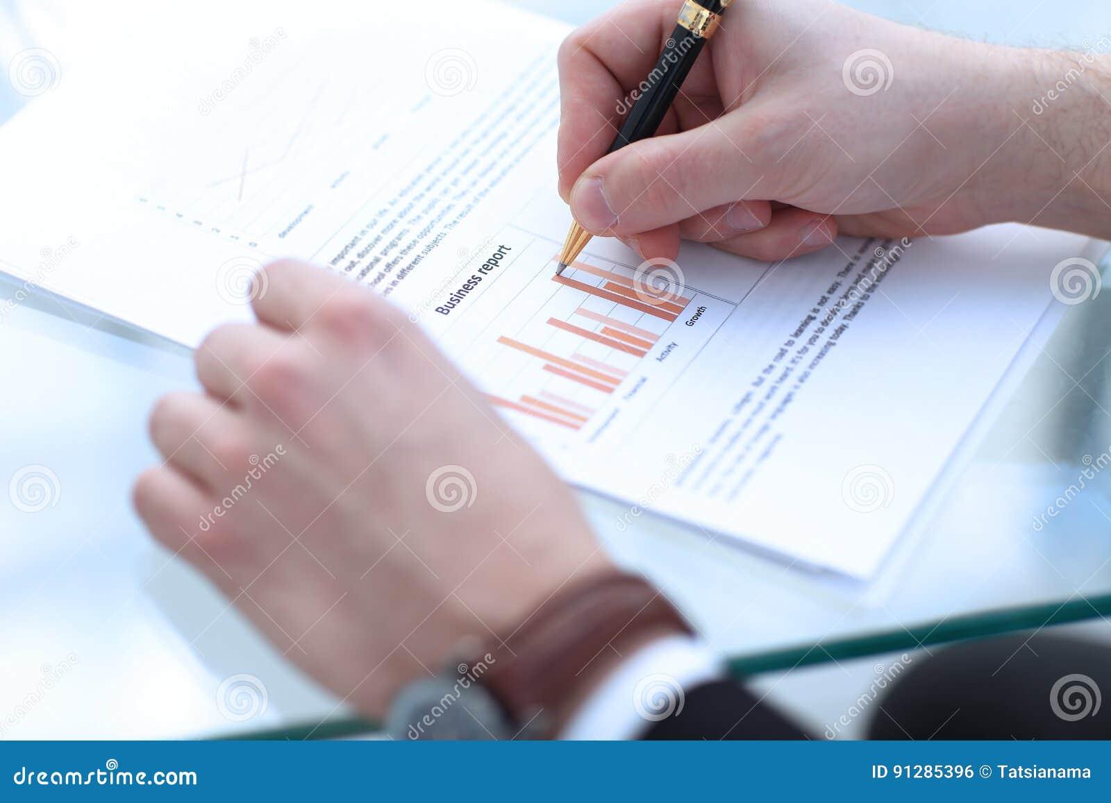 Den allvarliga affärsmannen som arbetar på att se för dokument, koncentrerade med portföljen och telefonen på tabellen
