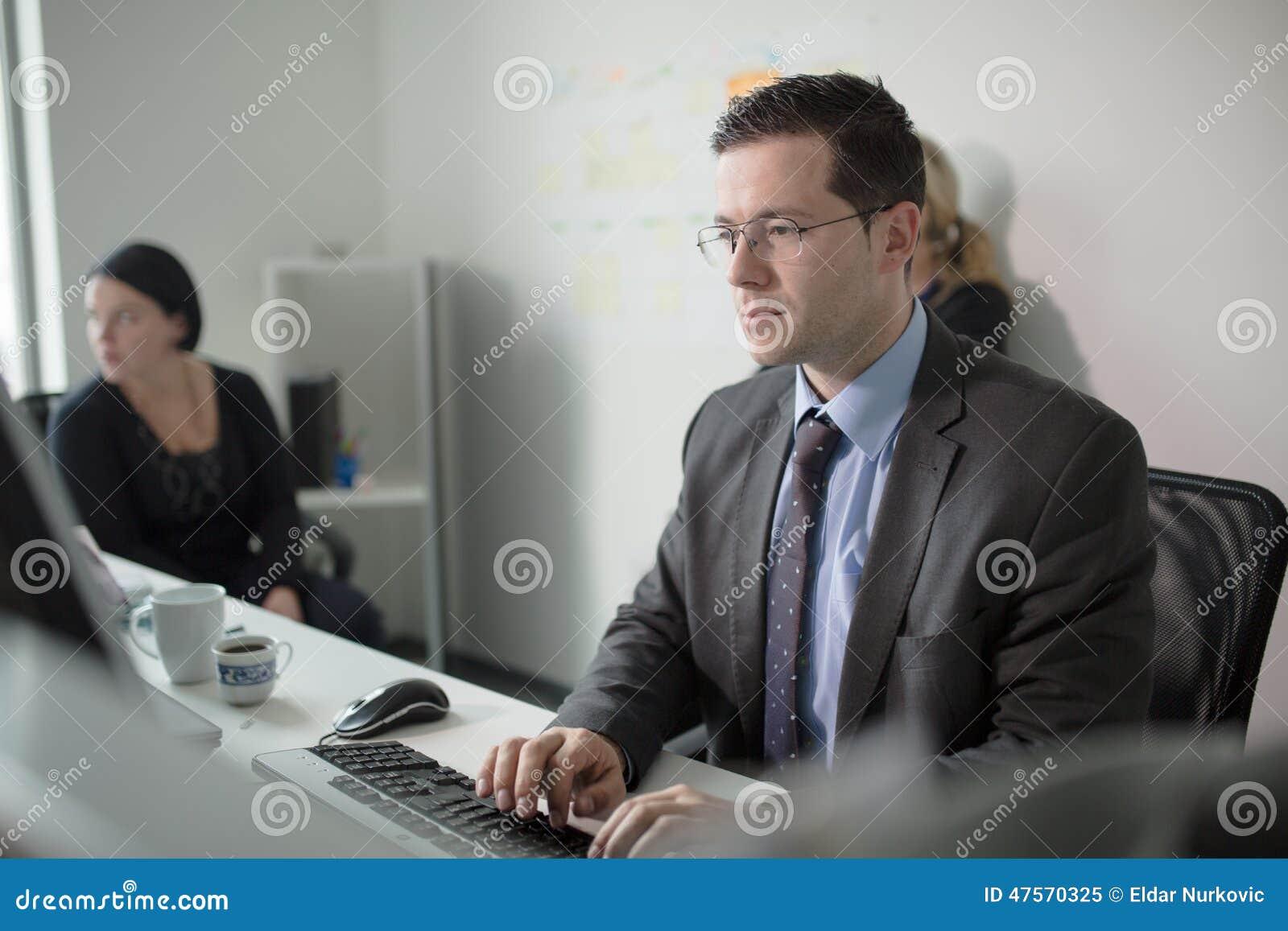 Den allvarliga hängivna affärsmannen arbetar i regeringsställning på datoren Verkligt ekonomaffärsfolk, inte modeller Bankanställ