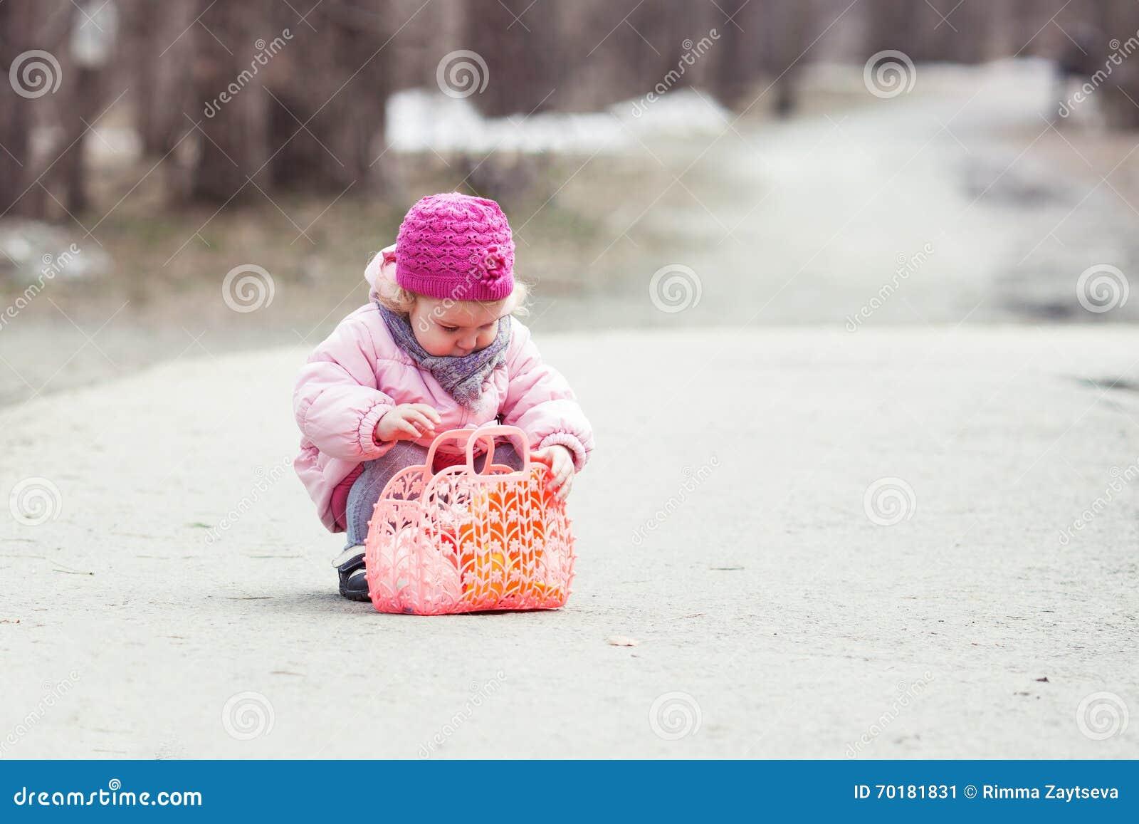 Den allvarliga härliga flickan som går med handväskan i vår, parkerar