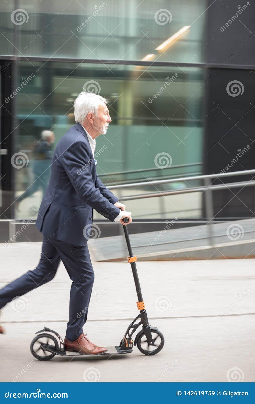 Den allvarliga höga affärsmannen som pendlar för att arbeta på, skjuter sparkcykeln