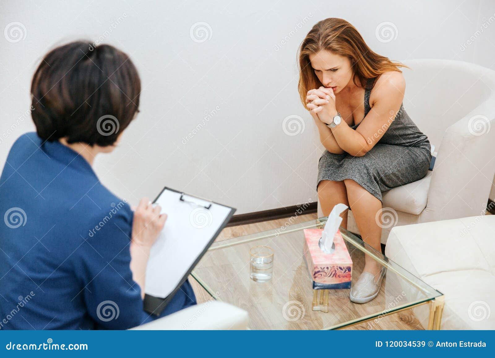 Den allvarliga och fundersamma flickan sitter på soffan och ser ner Hon rymmer munnen för handen nästan Hon är tänkande… som dig,