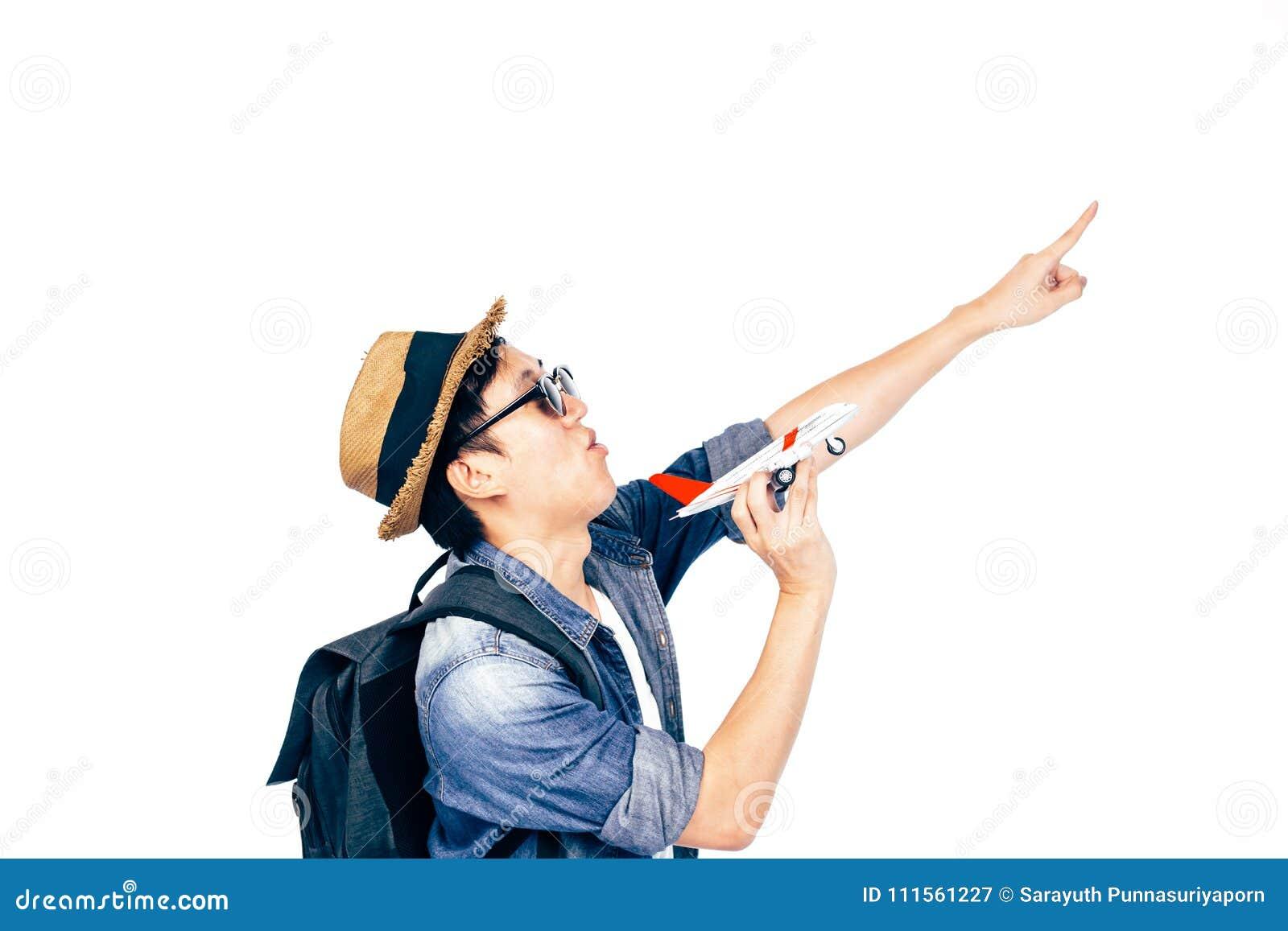 Den ambitiösa unga turisten som upp till pekar himlen som drömmer för att resa, isolerade över vit bakgrund