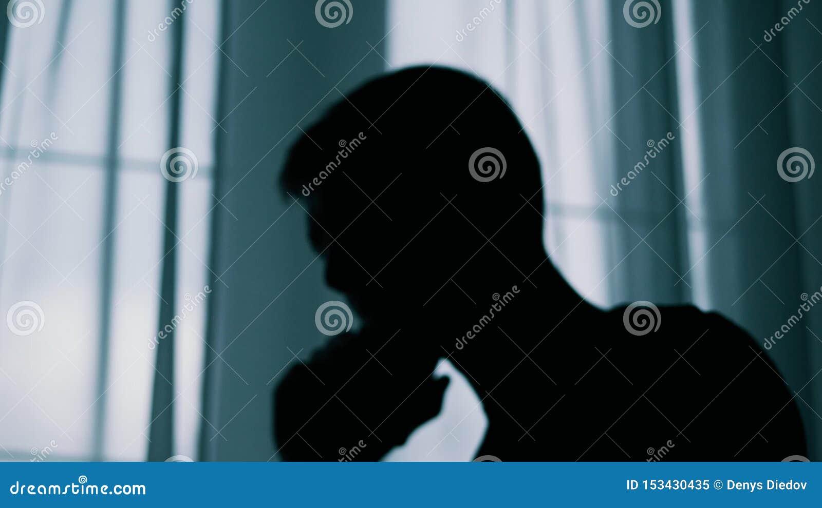Den anonyma suddiga konturn av en man som talar på en mobiltelefon, en brottsling, framtvingar pengar stock video