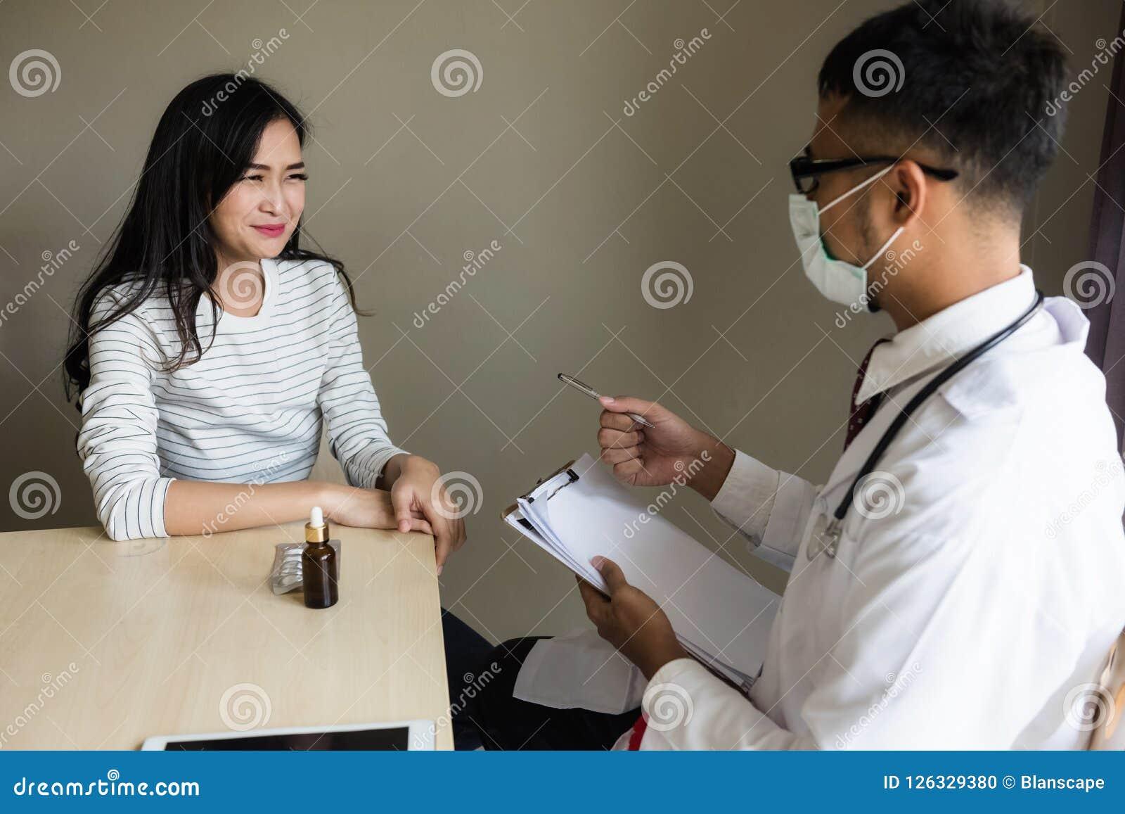 Den asiatiska doktorn diagnostiserar den patiient kvinnan i sjukhus